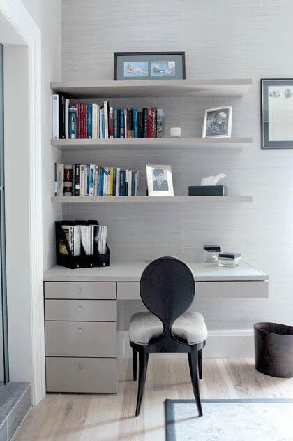 Escritório com escrivaninha e prateleiras brancas