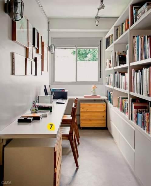 Escritório com estante de livros e mesa longa